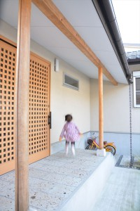 玄関前の大きな庇のある空間はとても便利です。大雨の日も濡れずに傘をたためるし、全天候対応の子供の遊び場にもなっています。